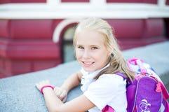 Pequeña muchacha sonriente hermosa en una calle de la ciudad del fondo Imagen de archivo