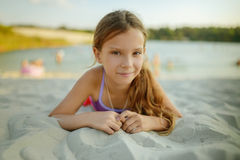 Pequeña muchacha sonriente hermosa que miente en la arena caliente Fotos de archivo