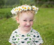 Pequeña muchacha sonriente linda en la guirnalda de la manzanilla imagen de archivo libre de regalías