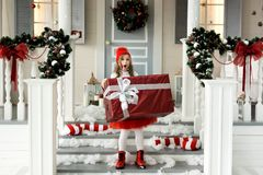 Pequeña muchacha sonriente linda feliz con la caja de regalo de la Navidad Feliz Navidad y buenas fiestas fotos de archivo