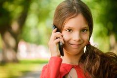 Pequeña muchacha sonriente que habla en el teléfono celular Imagen de archivo libre de regalías
