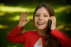 Pequeña muchacha sonriente que habla en el teléfono celular Foto de archivo libre de regalías