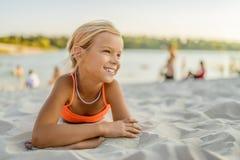 Pequeña muchacha sonriente que miente en la arena en la playa de la ciudad Fotos de archivo