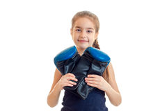 Pequeña muchacha sonriente que mira la cámara y que sostiene guantes de boxeo grandes Fotos de archivo libres de regalías