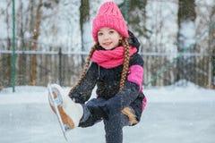 Pequeña muchacha sonriente que patina en el hielo en desgaste rosado Invierno Foto de archivo libre de regalías