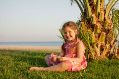 Pequeña muchacha sonriente que se sienta cerca de la palmera en la playa. Imagen de archivo
