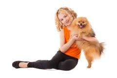 Pequeña muchacha sonriente que sostiene su perro Imagen de archivo