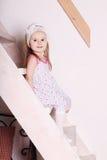 Pequeña muchacha sonriente rubia en el vestido que se sienta en las escaleras de madera Imágenes de archivo libres de regalías