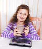 Pequeña muchacha triguena que usa el ordenador de la tablilla Imagen de archivo