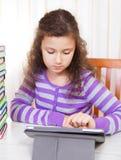 Pequeña muchacha triguena que usa el ordenador de la tablilla Imagenes de archivo
