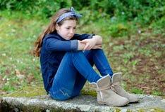 Pequeña muchacha triste con diez años que se sientan en un banco Fotografía de archivo