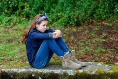 Pequeña muchacha triste con diez años que se sientan en un banco Imagenes de archivo