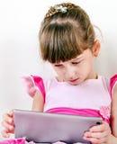 Pequeña muchacha triste con una tableta Imágenes de archivo libres de regalías