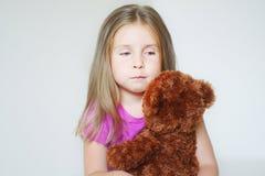 Pequeña muchacha triste que abraza un oso de peluche Imágenes de archivo libres de regalías