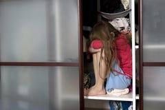 Pequeña muchacha triste que se sienta dentro de guardarropa Imagenes de archivo