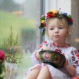 Pequeña muchacha ucraniana en vestido nacional con la comida tradicional Foto de archivo libre de regalías