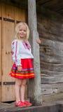 Pequeña muchacha ucraniana que se coloca cerca de casa de madera nacional vieja Imagen de archivo libre de regalías