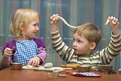 Pequeña muchacha y la ayuda del muchacho en cocina Imagenes de archivo