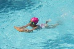 Pequeña natación de la chica joven en una piscina Fotos de archivo libres de regalías