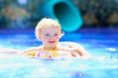 Pequeña natación hermosa de la muchacha en la piscina Fotos de archivo
