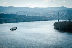 Pequeña navegación del buque de carga en el río Danubio cerca del puente en Novi Sad, Serbia Imagenes de archivo