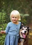 Pequeña niña pequeña linda que juega afuera con su perro casero en fotos de archivo