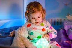 Pequeña niña pequeña linda que juega con la lámpara colorida de la luz de la noche antes de irse a la cama Hija cansada soñolient imágenes de archivo libres de regalías