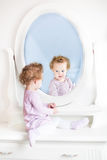 Pequeña niña pequeña linda con el pelo rizado que mira en espejo imagen de archivo libre de regalías