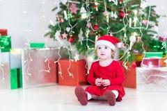 Pequeña niña pequeña linda en un sombrero de santa debajo del árbol de navidad Imágenes de archivo libres de regalías