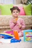 Pequeña niña pequeña linda que juega con el juguete en sitio fotos de archivo