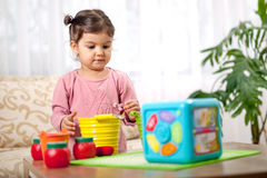 Pequeña niña pequeña linda que juega con el juguete en sitio fotografía de archivo libre de regalías