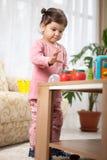 Pequeña niña pequeña linda que juega con el juguete en sitio fotografía de archivo