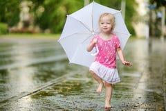 Pequeña niña pequeña linda que se divierte debajo de una lluvia fotos de archivo libres de regalías