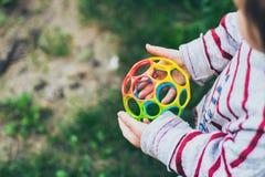 Pequeña niña pequeña que sostiene la bola colorida Imagenes de archivo