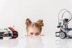 Pequeña persona femenina sonriente curiosa alegre cerca de los juguetes modernos Imágenes de archivo libres de regalías