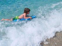 Pequeña persona que practica surf Imagen de archivo