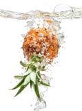 Pequeña piña que cae en agua en blanco Fotos de archivo