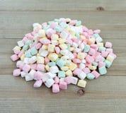 Pequeña pila de mentas en colores pastel de la mantequilla en un fondo de madera foto de archivo libre de regalías