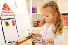 Pequeña pintura de la muchacha del artista en lona del papel grande Foto de archivo libre de regalías