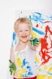 Pequeña pintura sucia del niño con la imagen de la brocha en el caballete Educación creatividad Escuela pre-entrenamiento Retrato imagen de archivo libre de regalías