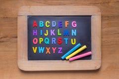 Pequeña pizarra con las tizas y los alfabetos ingleses o del color del color Fotos de archivo