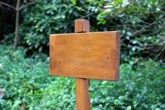 Pequeña placa de madera contra un fondo verde Imagenes de archivo