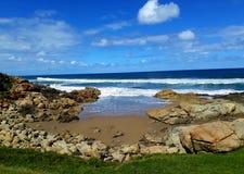 Pequeña playa con el océano azul debajo del cielo azul fotografía de archivo