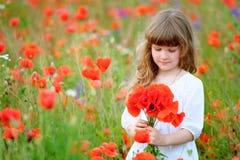 Pequeña princesa con las flores rojas salvajes en el campo fotografía de archivo