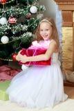 Pequeña princesa con un regalo por el árbol de navidad Imagen de archivo libre de regalías