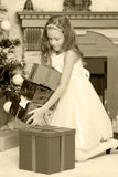 Pequeña princesa con un regalo por el árbol de navidad Fotos de archivo
