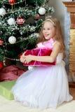 Pequeña princesa con un regalo por el árbol de navidad Fotografía de archivo