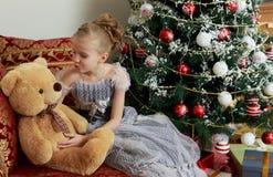Pequeña princesa en la víspera del ` s del Año Nuevo con un oso de peluche Imagen de archivo
