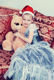 Pequeña princesa en la víspera del ` s del Año Nuevo con un oso de peluche Foto de archivo libre de regalías