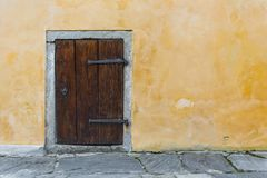 Pequeña puerta de madera vieja en la pared rústica amarilla Fotos de archivo libres de regalías